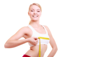 woman measure breast size after using breast enlargement pills
