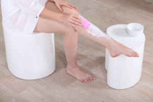 woman putting revitol hair removal cream on her leg